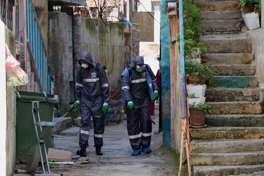 Trabajadores de la agencia de la ONU para los refugiados palestinos llevan a cabo una desinfección de las calles para prevenir la propagación del COVID-19 en los campos de refugiados.