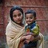 Une jeune fille rohingya tient son frère dans ses bras devant un club pour les jeunes à Cox's Bazar, au Bangladesh.