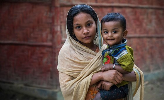 अपने भाई को गोद में लिये हुए एक शरणार्थी लड़की.