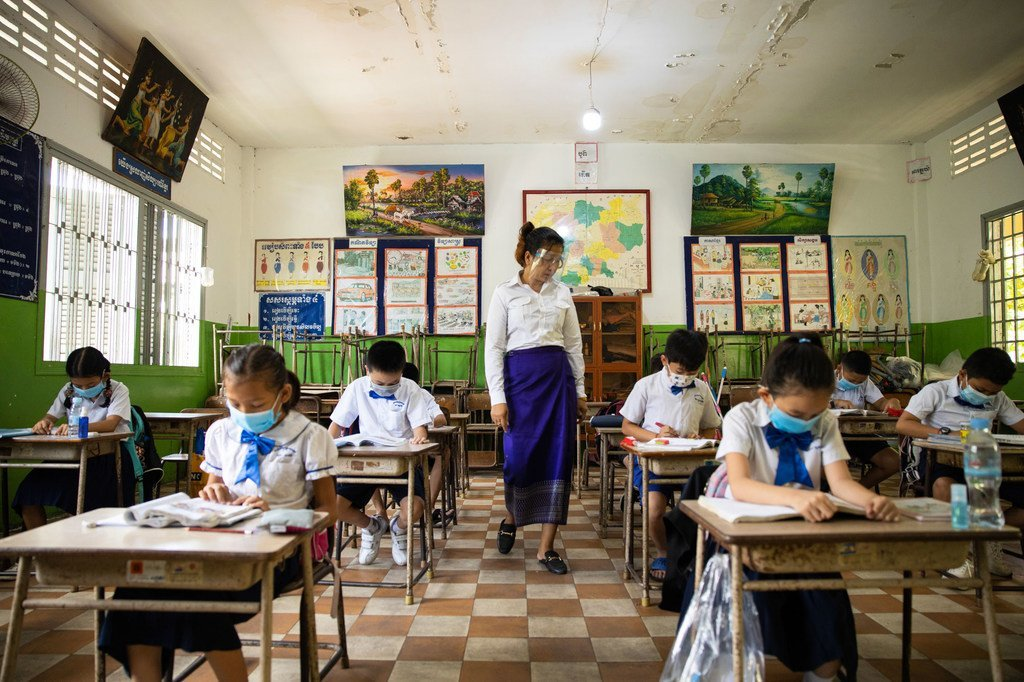 Des enseignants et des élèves portent des masques faciaux et maintiennent une distance physique dans une école au Cambodge.