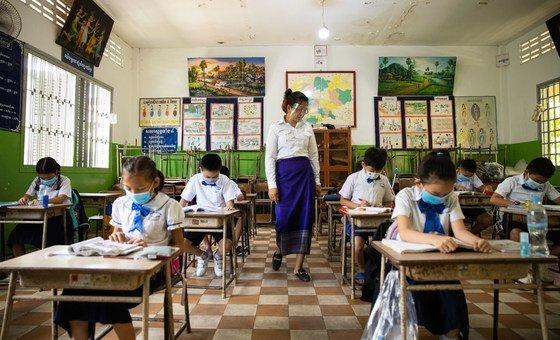 Professores e alunos, de máscara, em escola reaberta no Camboja
