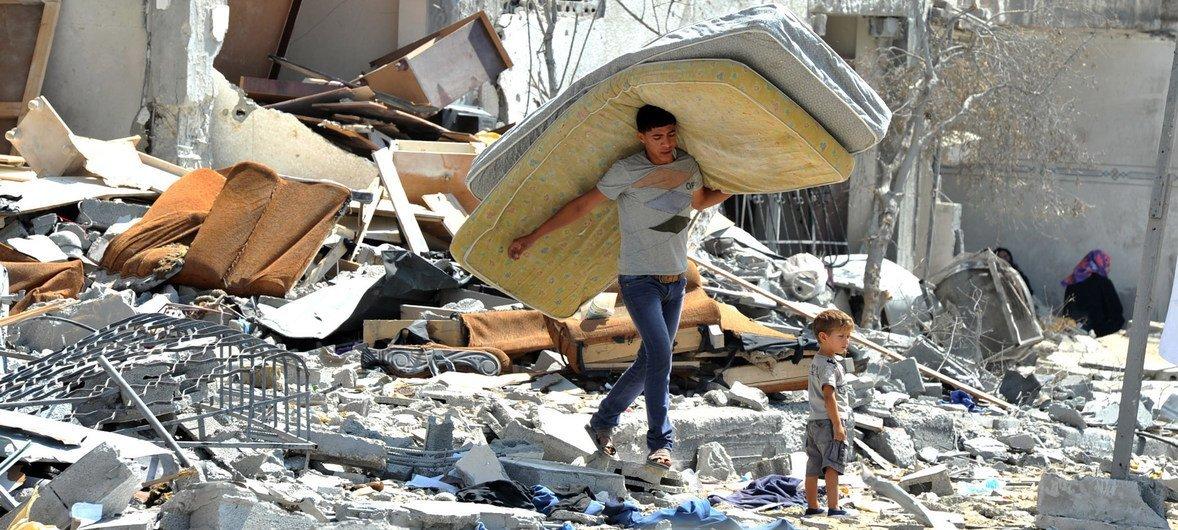 गाज़ा पट्टी में इसराइली हमले में क्षतिग्रस्त घर से सामान निकालता एक फ़लस्तीनी किशोर.(फ़ाइल फ़ोटो)