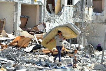 गाज़ा पट्टी में इसराइली कार्रवाई में क्षतिग्रस्त घर से सामान निकालता एक फ़लस्तीनी किशोर.
