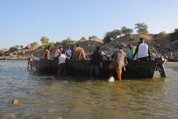 Refugiados etíopes fugindo de confrontos na região de Tigray cruzam a fronteira com Hamdayet, NO Sudão, sobre o rio Tekeze.