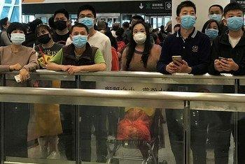 Gente con mascarillas para protegerse del coronavirus espera en la zona de llegadas del aeropuerto internacional de Shenzhen Bao'an