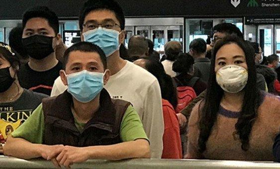 Des personnes portant un masque alors qu'ils attendent dans le hall des arrivées à l'aéroport international de Shenzhen, en Chine.