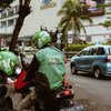 Все больше людей находят работу на цифровых платформах. На фото - мотоциклист в Индонезии ждет пассажира, вызвавшего его через популярное приложение Go Jek.