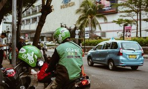 A motorcycle rider from an Indonesian transportation startup waits for  a passenger.