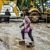 Mulher atravessa uma estrada inundada em El Salvador, depois que a tempestade tropical Amanda causou um deslizamento de terra