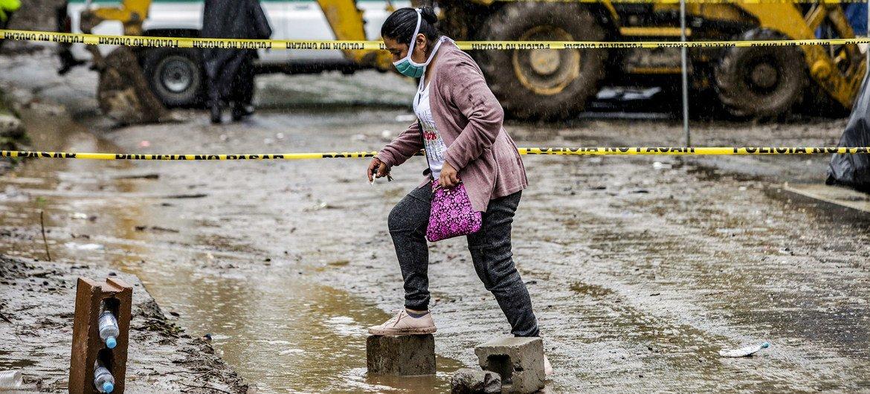A pistillate   walks crossed  a flooded roadworthy  successful  Santo Tomás, San Salvador, aft  Tropical Storm Amanda caused a landslide.