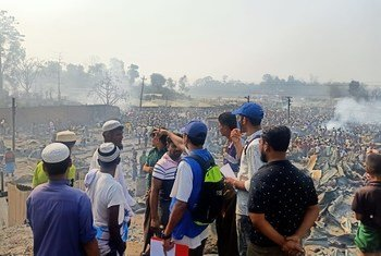 IOM personnel at Kutupalong refugee camp in Bangladesh. In the background are the tens of thousands of refugees displaced after the fire.