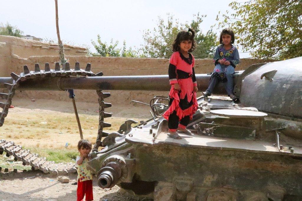 Des enfants à Kandahar, en Afghanistan, jouent sur un char détruit, témoin de la guerre passée avec l'Union soviétique.