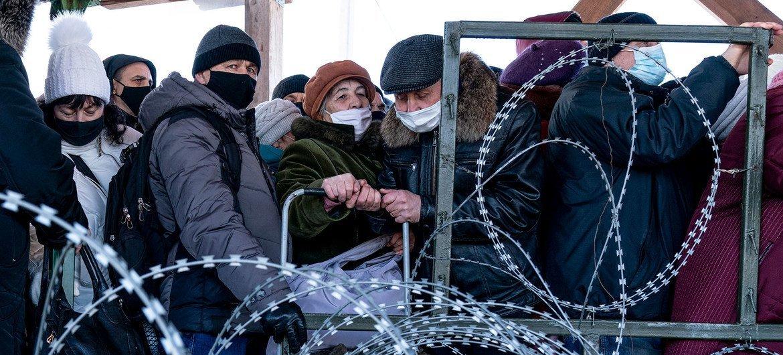 In Ukraine, residents wait in line at the Novotroitske crossing point.