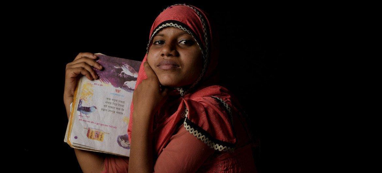 一名十四岁的罗兴亚难民女孩在孟加拉国考克斯巴扎的一个难民营里拿着她最喜欢的诗集。