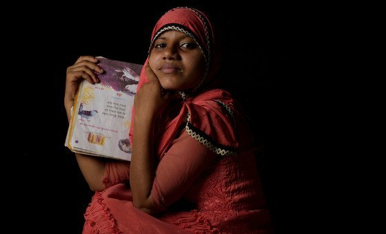 A fourteen year-old Rohingya refugee holds her favorite book of poetry at a refugee camp in Cox's Bazaar, Bangladesh.