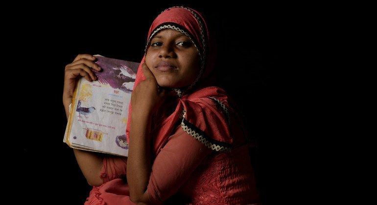 لاجئة من الروهينجا تبلغ من العمر أربعة عشر عاما تحمل كتاب الشعر المفضل لديها، في مخيم للاجئين في كوكس بازار، بنغلاديش.