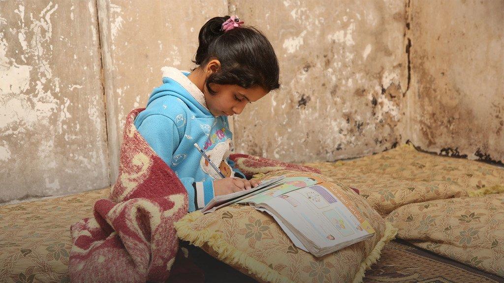 فتاة فلسطينية لاجئة في مخيم درعا في سوريا، تواصل دراستها رغم تعطل المدارس بسبب جائحة كوفيد-19.