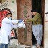 أحد طواقم الأونروا يقدم الدواء لرجل فلسطيني مسن في قطاع غزة.