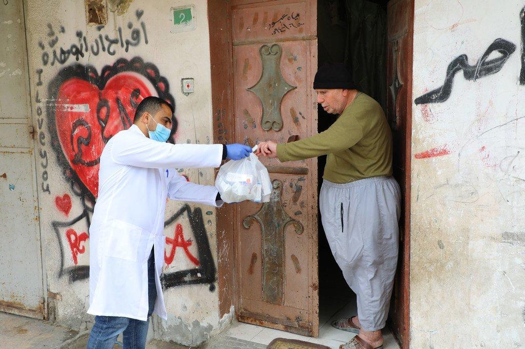 Photo : UNRWA/Khalil Adwan Un employé de l'UNRWA apporte des médicaments à un homme âgé dans la bande de Gaza.