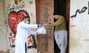 An UNRWA staff member provides medication to an elderly Palestine man in the Gaza strip.