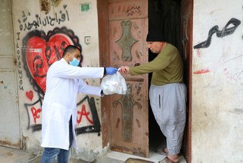 Un trabajador de UNRWA le ayuda con medicamentos a un anciano palestino en la Franja de Gaza.