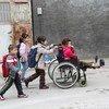 一个坐在轮椅上的残疾难民女孩在姐姐帮助下和其他兄弟姐妹前往土耳其阿达纳上学。