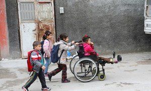 A disabled refugee girl from Syria in a wheelchair is helped by her sister as she and her other siblings head to school in Adana, Turkey.