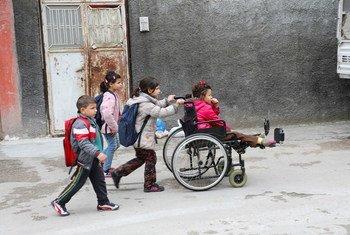 طفلة لاجئة من ذوي الإعاقة تجلس على كرسي متحرك تساعدها أختها بينما تتوجه هي وأشقاؤها إلى المدرسة في أضنة، تركيا.