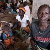 En République démocratique du Congo, Jeanette Buse Lasi, veuve et mère de quatre enfants, est assise avec ses enfants dans un abri communal dans un camp de personnes déplacées à Bunia.