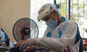 Trabajador de salud revisando a un niño colombiano durante la pandemia de COVID-19.