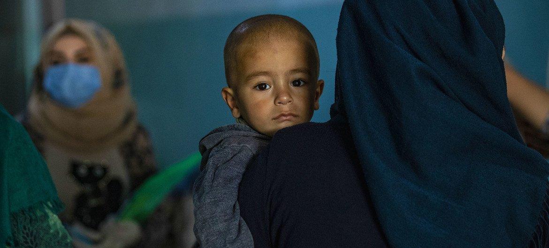 أم تحمل طفلها في مركز في مخيم الحسكة، حيث تقدم اليونيسف معلومات أساسية بشأن الوقاية من كوفيد-19.
