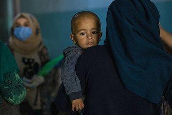 Una madre sostiene a su hijo en un refugio de Hassakeh (Siria), donde voluntarios del UNICEF proporcionan información esencial sobre la protección contra COVID-19.