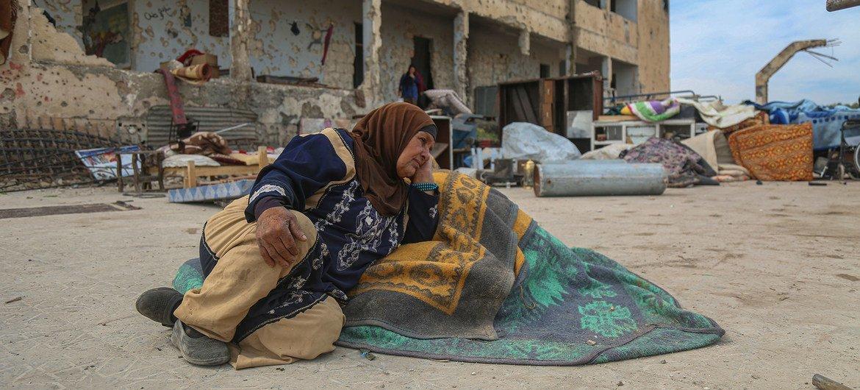 امرأة نازحة في إدلب السورية تجلس على الأرض في مدرسة مدمرة.