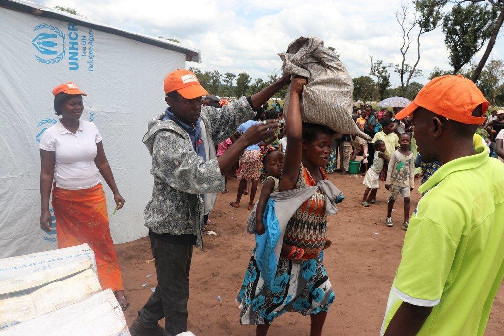 En mars 2018, des travailleurs humanitaires fournissent des rations alimentaires à des réfugiés du camp de Lovua, en Angola.