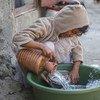 طفل في اليمن يغسل الأواني في أحد مخيمات النزوح بعد استعادة إمدادات المياه.