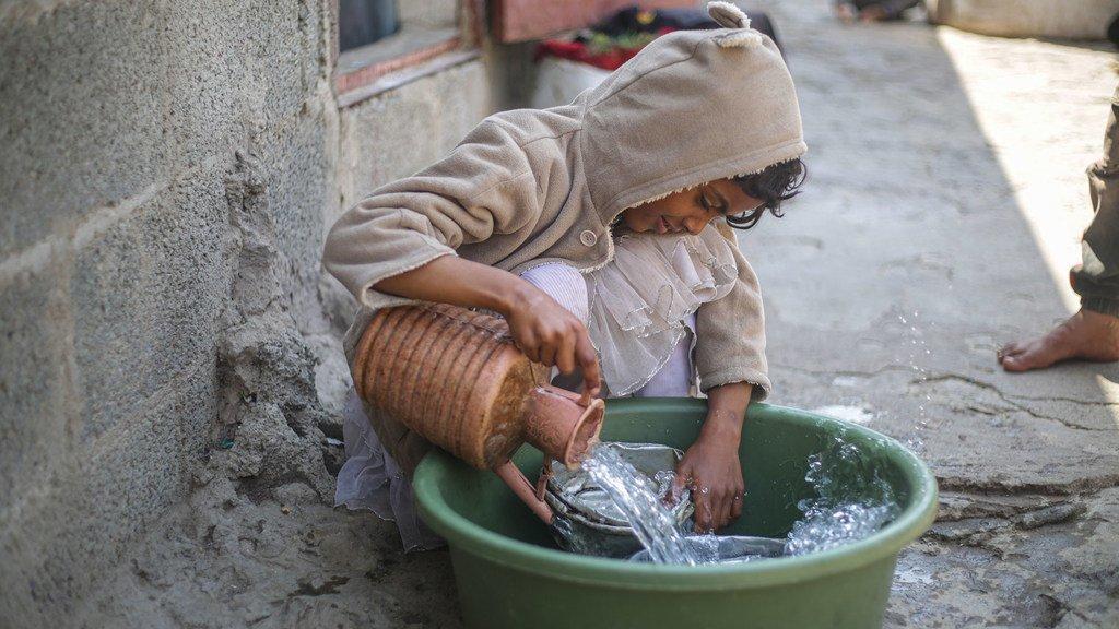 Un enfant déplacé lave des ustensiles de cuisine dans un camp au Yémen.