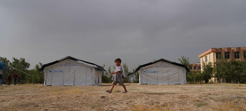 एक बच्चा अफगानिस्तान में असुरक्षा के कारण अपने परिवार के यूनिसेफ के विस्थापित होने के बाद काबुल में स्थापित एक अस्थायी शिविर से गुजरता है।