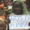 A young girl holds a sign that says Zo Kwe Zo, Central African Republic's national motto, meaning all human beings are equal.