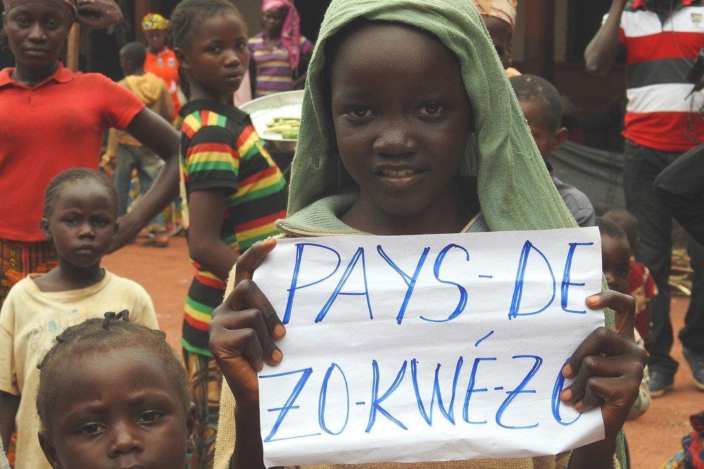En République centrafricaine, une fillette tient un papier sur lequel est écrit Zo Kwe Zo, qui veut tous les êtres humains sont égaux.