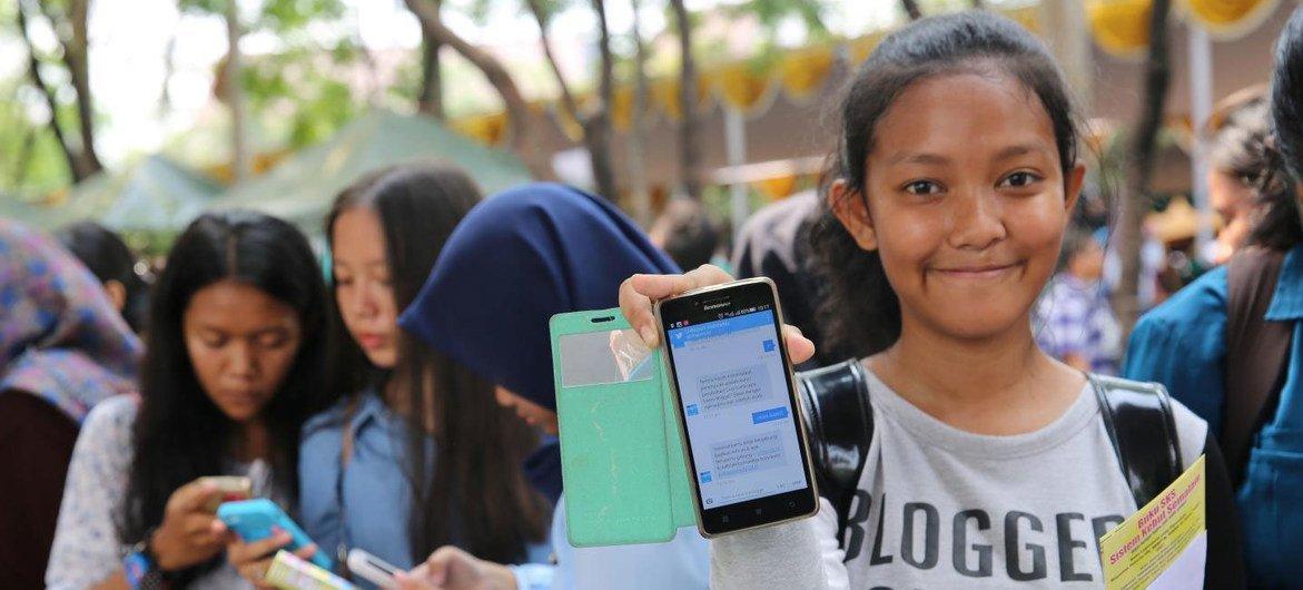 印度尼西亚少女在使用智能手机。