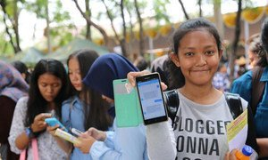 Indonesian adolescent girls use their smartphones.