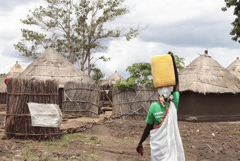 Uganda hosts the largest number of refugees in Africa. Pictured here, a South Sudanese refugee returns to her shelter after fetching water from a community tap at a refugee settlement in Adjumani district. (file photo)