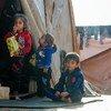 أطفال يحتمون من البرد مع أسرهم في مخيم غير رسمي في سوريا، قرب الحدود مع تركيا.