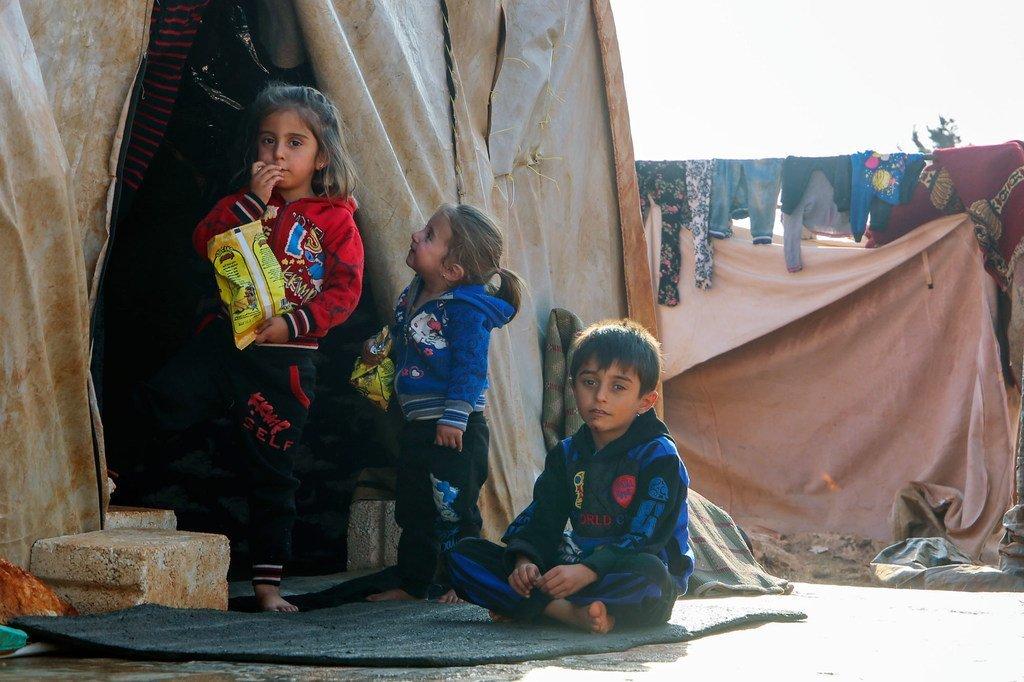 在与土耳其接壤的叙利亚一个非正式定居点中,儿童与他们的家人试图躲避严寒。