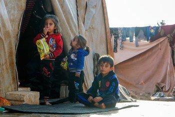Crianças se abrigam do frio cem um assentamento informal em Killi, na Síria, perto da fronteira com a Turquia.