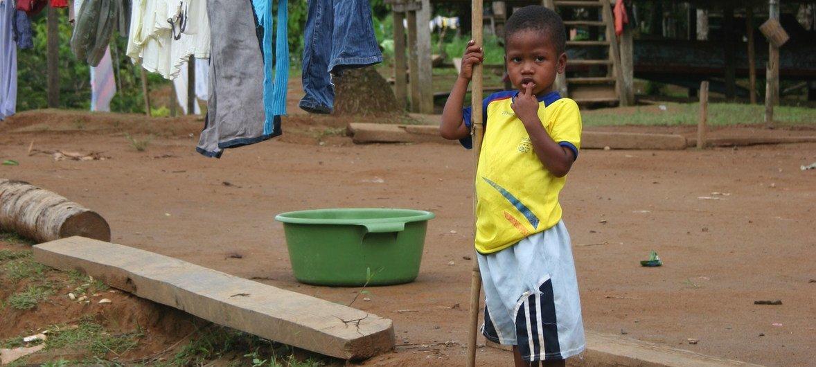 Un niño posa al frente de su hogar en Cayapas, Ecuador.