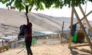 خلف هذه الصبية الفلسطينية التي تقوم بأعمال منزلية، منطقة محظورة على الفلسطينيين