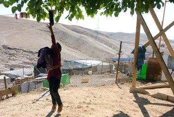 一名巴勒斯坦女孩正在收晾干的衣服,她身后是以色列设立的巴勒斯坦人活动限制区。