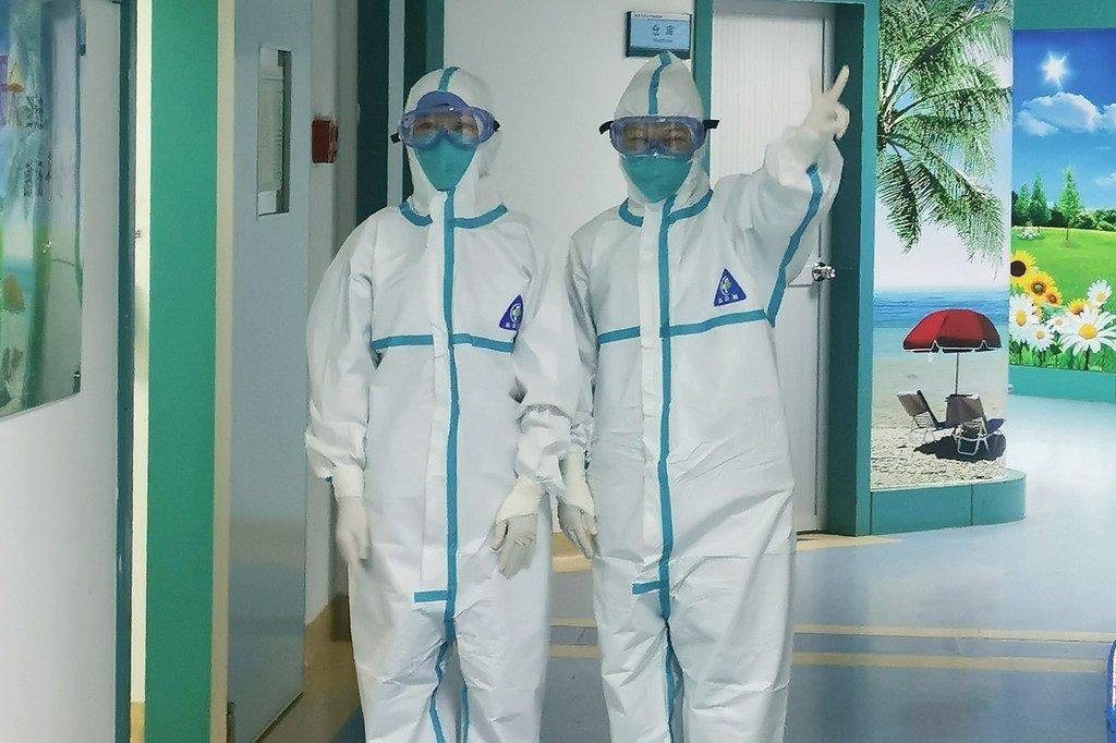 Deux agents de santé vêtus de vêtements de protection à l'Université médicale de Guangdong se préparent à admettre des patients infectés par le coronavirus.