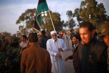 An old man holds Libya's revived flag during a military graduation ceremony in the western city of Zawia. December 2011.